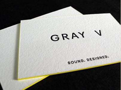 letterpress printed business card black ink on white paper with yellow edge paint