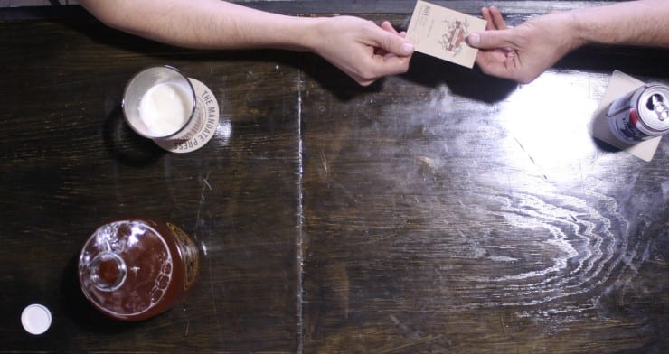 two people hand a letterpress business card over a table while drinking