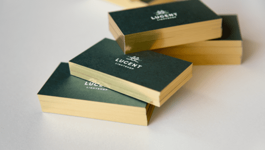 custom business cards with white foil on duplexed green and white paper with gold gilded edges
