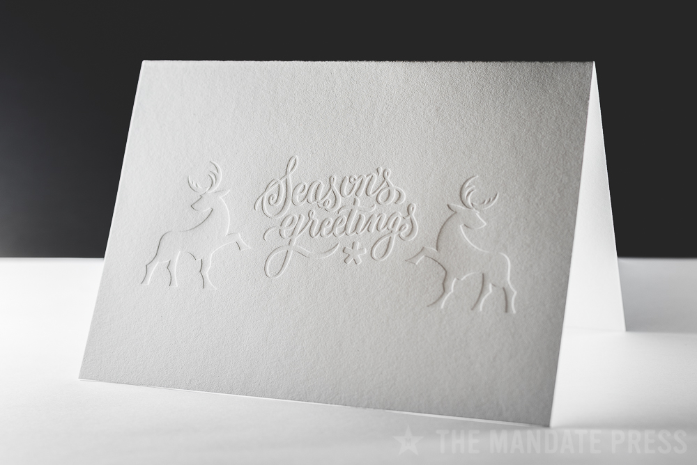 image of letterpress printed greeting card with blind seasons greetings deboss