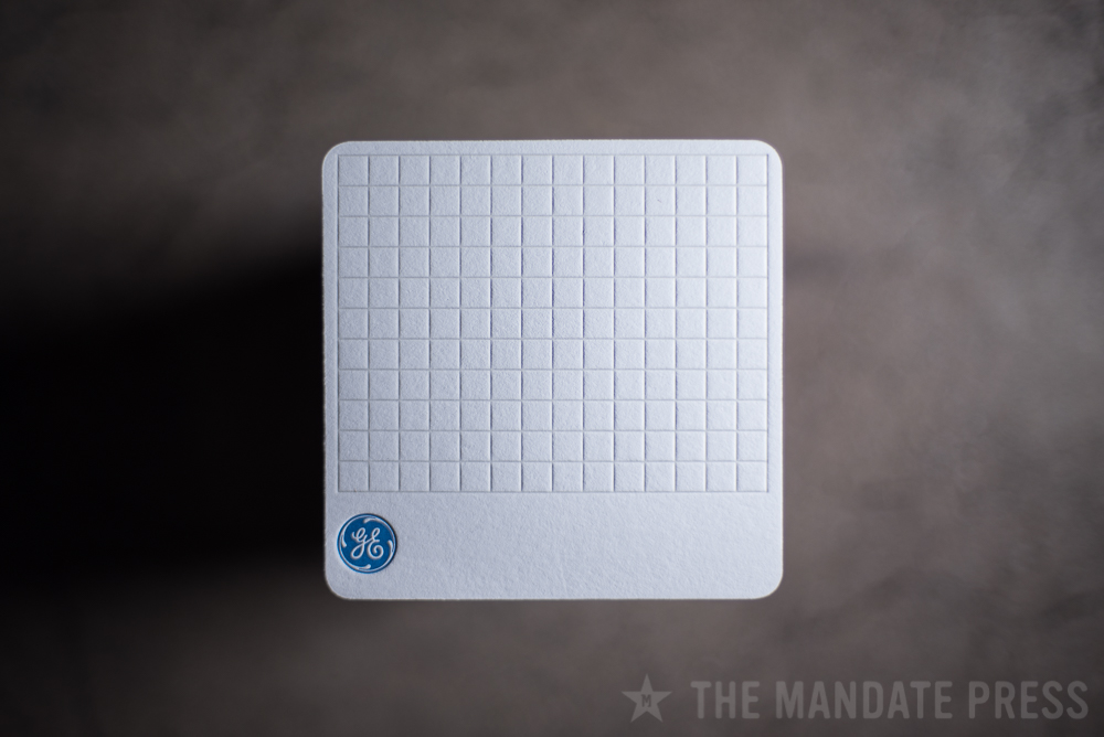 letterpress printed square coaster for General Electric with blind deboss pattern and blue logo