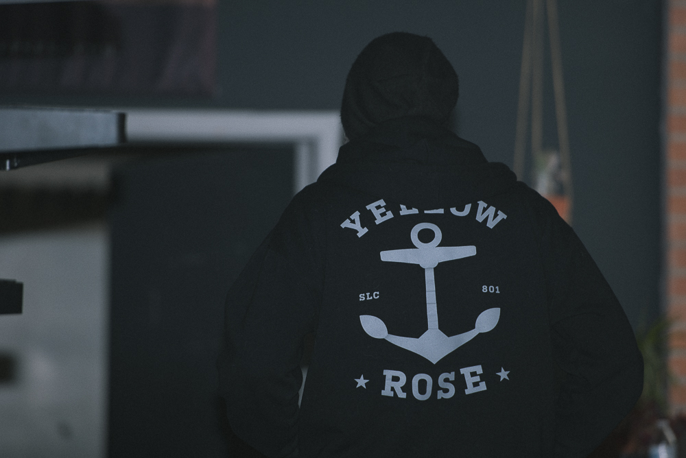 man wearing yellow rose tattoo hooded sweatshirt