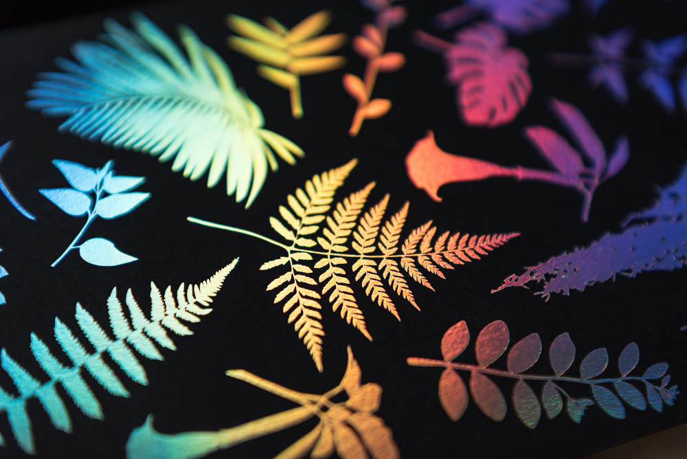 letterpress printed leaves on black paper with holographic foil shown at angle with color